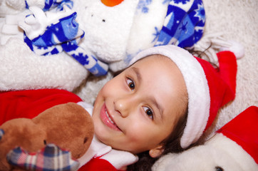 Beautiful smiling litle girl wearing a christmas clothes, hugging a moose and bear teddy, laying on a white blanket
