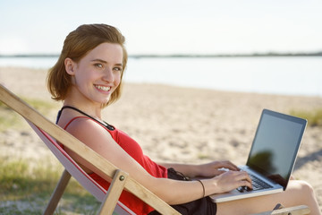 Smiling happy young woman working on a laptop