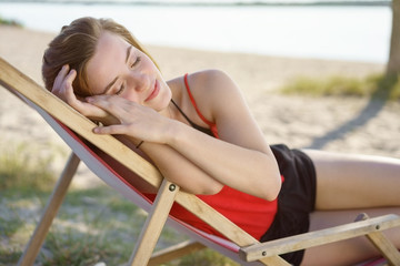 Attractive young woman taking a nap at the beach