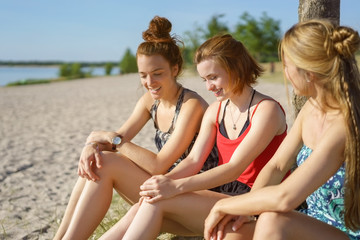 Three attractive young ladies relaxing at a beach