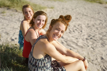 Three happy girlfriends relaxing on a sandy beach