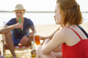 Young redhead woman drinking with friends