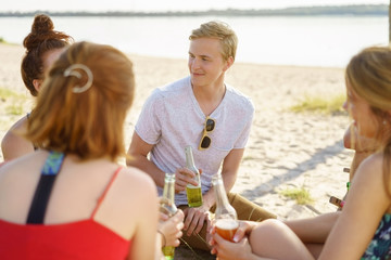 Young students chatting together on a summer beach