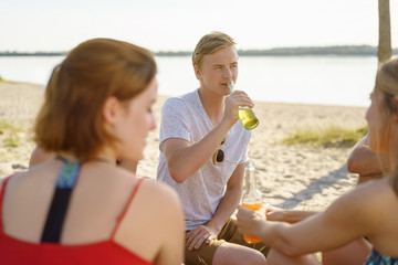 Young man enjoying a cool drink at the beach