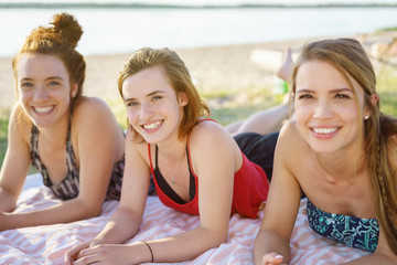 Three attractive women relaxing on a sandy beach