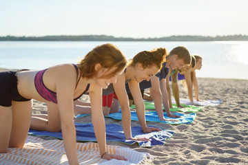 group of young people working out on a beach
