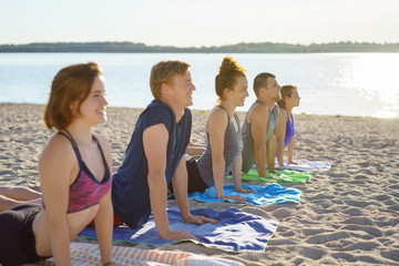 young friends practising yoga on a beach