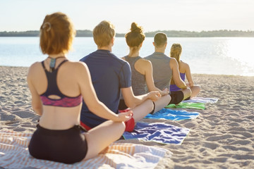 Row of young friends meditating on a beach