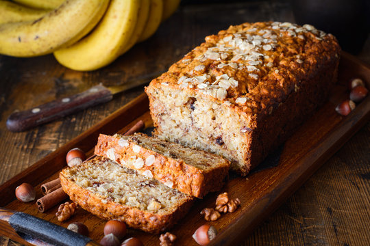 Banana bread with walnuts, cinnamon and chocolate chips on wooden tray. Closeup view, selective focus