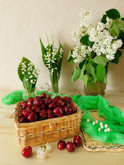 Cherries in a wicker basket and bouquet of lily of the valley in glasses