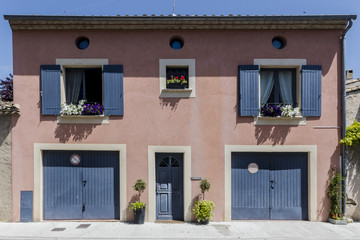 Pink french house in southern France with dark grey shutters and doors and flower pots at windows