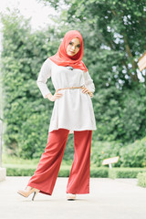 Fashion portrait of young beautiful muslim woman with the red  hijab.