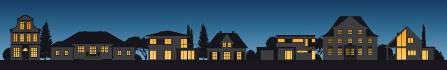Verschiedene Häsuer mit leuchtenden Fenstern bei Nacht