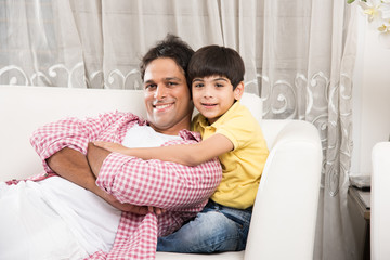 Family time - portrait picture of handsome indian father and son while sitting on a sofa, indoor. Selective focus