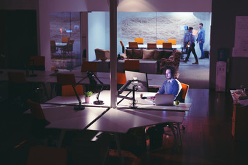 man working on computer in dark office