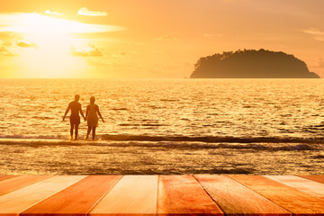 Deurstickers Egypte Wood plank with silhouette of couple on the beach against sunset. Summer concept.