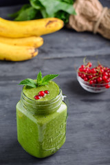 Healthy green spinach smoothie in a jar mug decorated with mint and red currant berries with ingredients on the black wooden table. Selective focus. Detox concept.