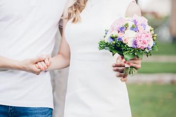 bride's hands hold beautiful wedding bouquet