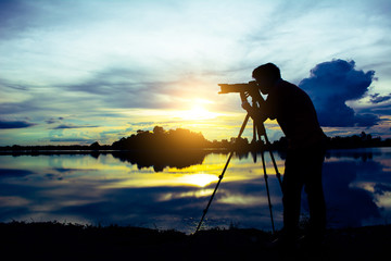 silhouette of a photographer who shoots a sunset in the river
