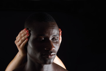 a hand covering a ears of african man on black