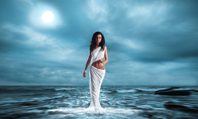 Fashion shoot of Aphrodite styled young woman over ocean background.