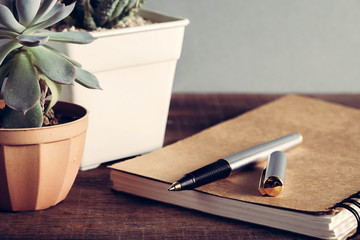 pen and book on wood background with filter effect retro vintage style