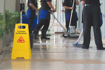 Cropped image of woman in protective gloves using a flat wet-mop and machine while cleaning floor