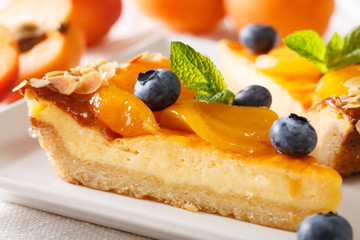 beautiful dessert: cheesecake with apricots, blueberries and almonds close-up. horizontal