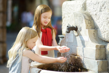 Two cute little girls playing with a drinking water fountain on warm and sunny summer day in Desenzano del Garda town