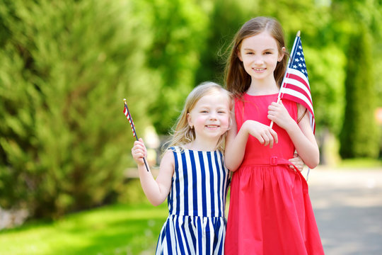 Two adorable little sisters holding american flags outdoors on beautiful summer day.