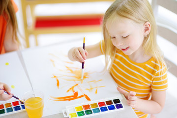 Cute little girl drawing with colorful paints at a daycare. Creative kid painting at school.