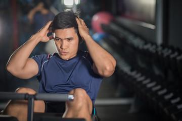 Asian man doing sit-ups at gym.