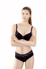 front portrait of young slim woman in black lingerie isolated on white background
