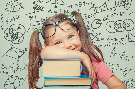 beautiful cute little genius girl with books. Math formulas, problems around her