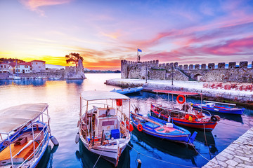 Old Greek port Nafpaktos with ancient harbor walls an background and fishing boats at foreground. Epic lilac colored sunrise sky over sea scenery. Nafpaktos is famous travel destination in Greece.