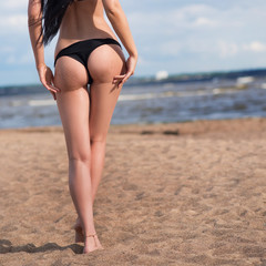 Sexual woman on the beach with stones and sand. Ass in bikini