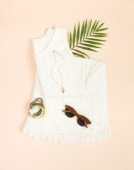 Summer fashion, summer outfit on cream background. White lace dress, retro sunglasses, wood bracelet. Flat lay, top view