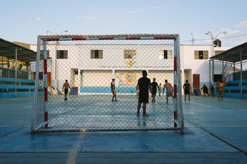 Boys playing soccer on the court