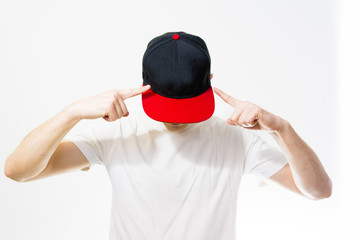 the man, guy in the blank black, red baseball cap, on a white background with white t shirt, mock up, free space, logo presentation