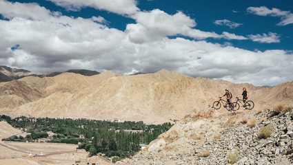 Two bicyclist traveler stay on mountain top