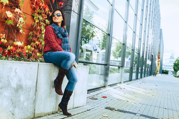 Wall Mural - Fashion wearing woman sits near modern shopping center