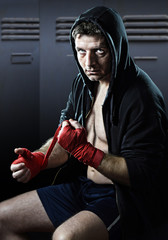 man in boxing hoodie jumper with hood on head sitting wrapping hands and wrists getting ready for fighting