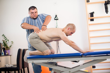 Man doing spine exercise with his therapist