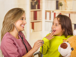 Beautiful smiling doctor examining with a stethoscope and a surprised little child in a hospital in a office background