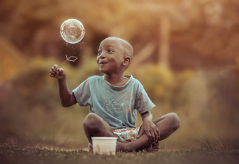 A young boy playing with a bubble.