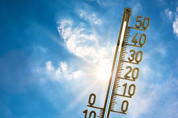Hitzewelle, Thermometer mit strahlender Sonne und blauem Himmel im Hintergrund