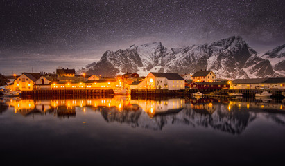 Lit houses reflected in an alpine lake.