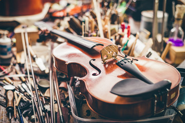 A violin sitting on a bench top covered in tools in a luthier's workshop.