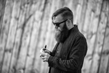 Vape man. E-liquid filling process. Outdoor portrait of a young brutal white guy with large beard vaping an electronic cigarette opposite the old wooden fence in the village. Black and white photo.