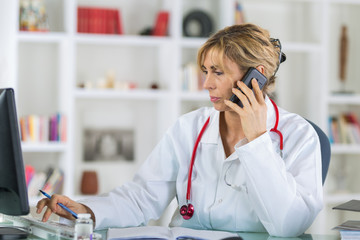 female doctor at her desk talking on phone